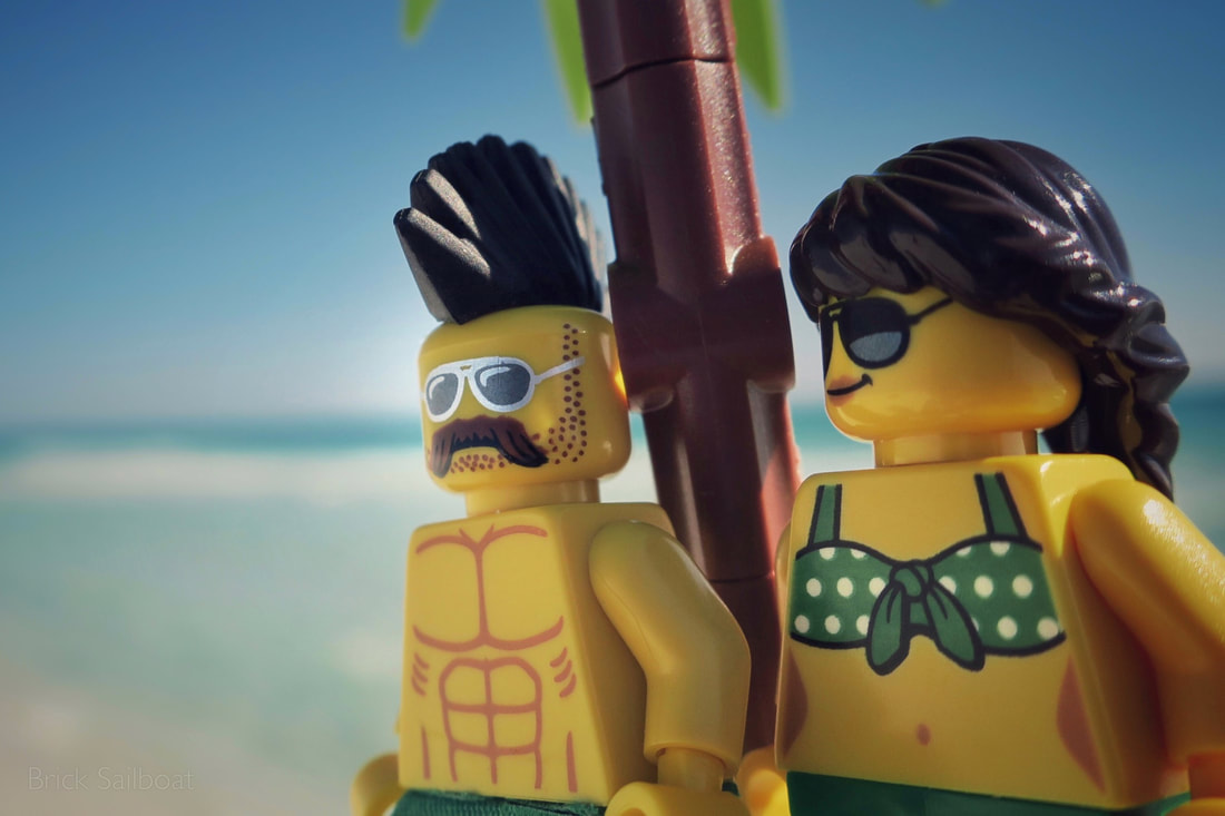 A LEGO stud and his girl dressed in green chill under the palm tree beachside